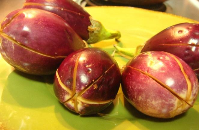 Brinjals slit and filled with drops of oil and salt.